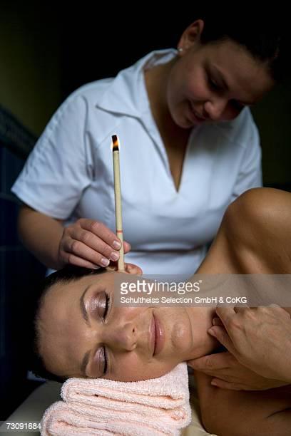Woman lying downhaving ear candling