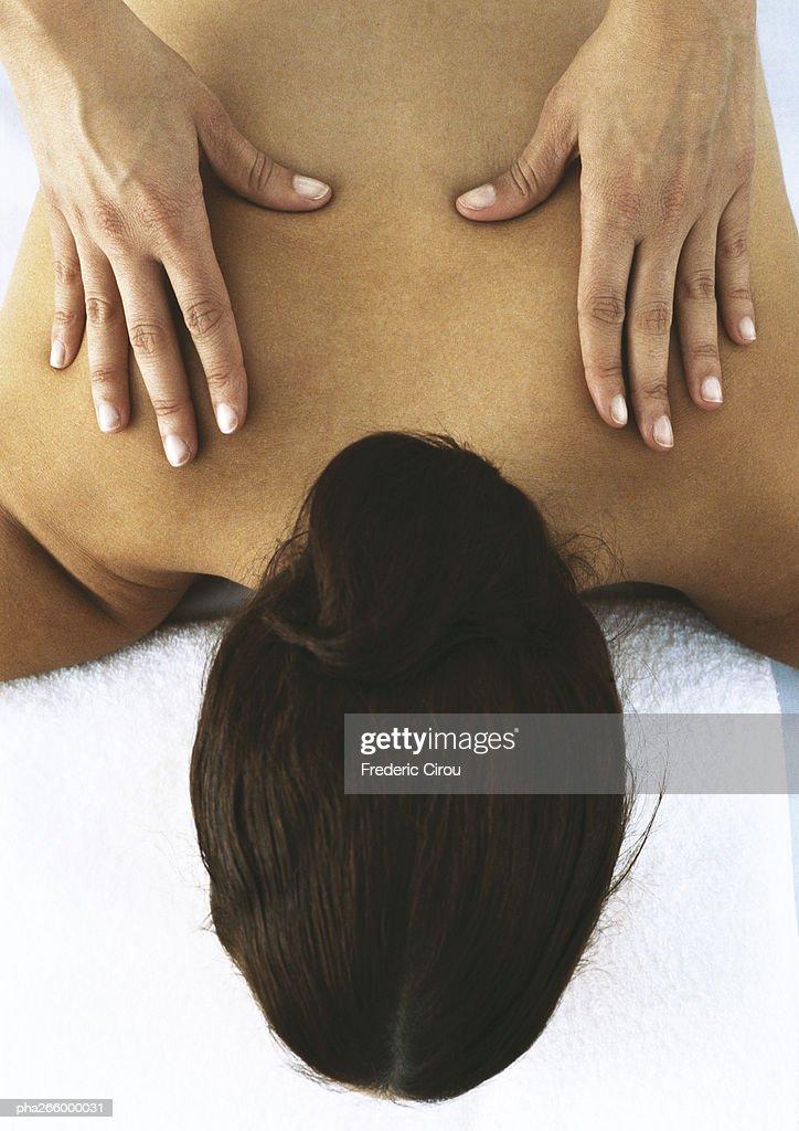 Woman lying face down, having back massaged : Stockfoto