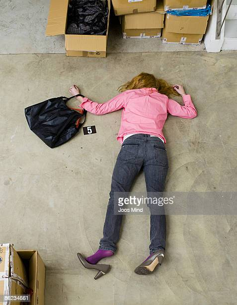 woman lying face down on storeroom floor, murdered - murdered women stock pictures, royalty-free photos & images
