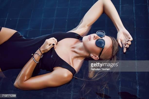 woman lying half-submerged in pool - costume da bagno foto e immagini stock