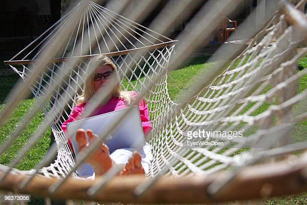 Woman lying in a hammock and working with a notebook on January 12, 2010 in Varkala near Trivandrum, Kerala, India.