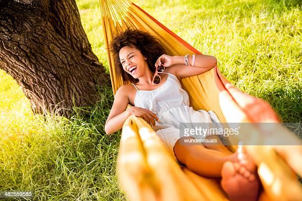 woman lying in a hammock laughing