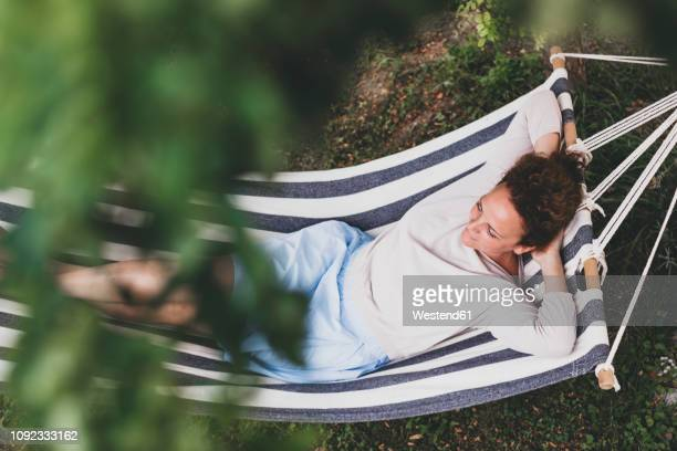 woman lying in a hammock - gelassene person stock-fotos und bilder
