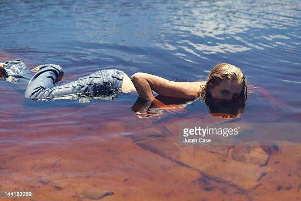 woman lying in a lake, half covered with water