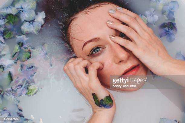 Woman lying in a milky bath with flowers