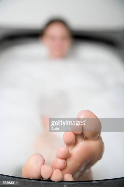 Woman lying in bathtub with feet resting on the edge