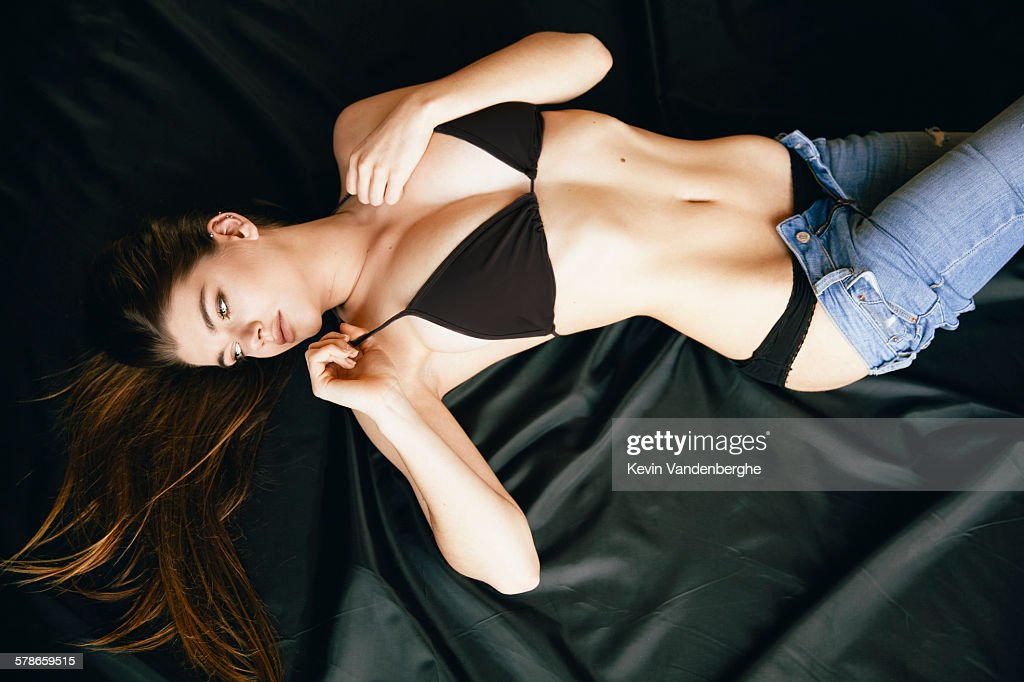 Woman lying in bed getting undressed : Stock Photo
