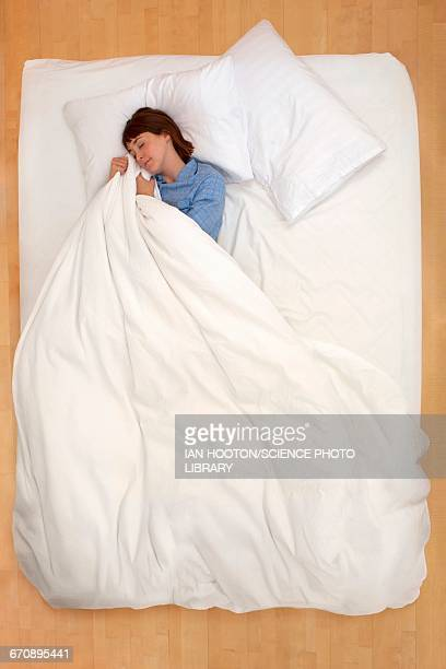 woman lying in bed holding duvet - duvet stock pictures, royalty-free photos & images