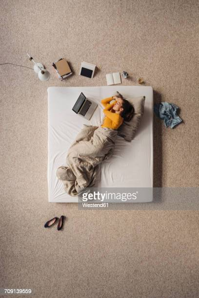 Woman lying in bed next to laptop, top view