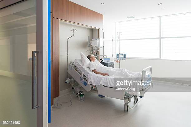 woman lying in bed on hospital ward - hospital ward stock pictures, royalty-free photos & images