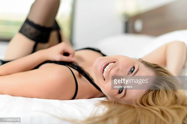 woman lying in bed - garter belts and stockings stock photos and pictures