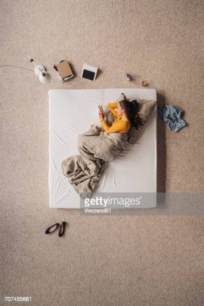 Woman lying in bed reading a book, top view