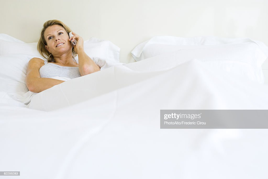 Woman lying in bed, talking on cell phone, looking away : Stock Photo