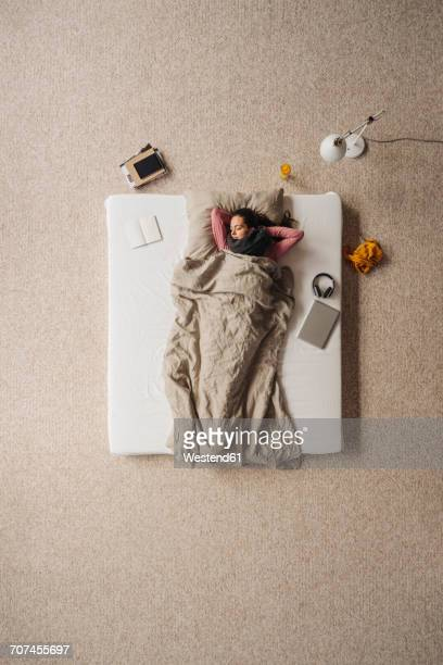 Woman lying in bed, top view