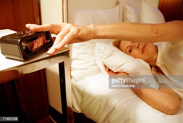 Woman lying in bed with hand on alarm clock