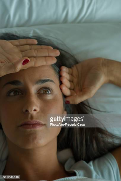 Woman lying in bed with hand on forehead