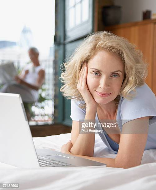 woman lying in bed with laptop and man in background on balcony - 50 59 years stock pictures, royalty-free photos & images