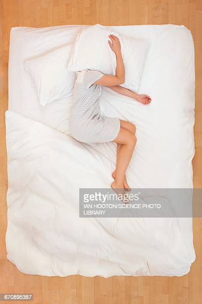 woman lying in bed with pillow over head - position stock-fotos und bilder