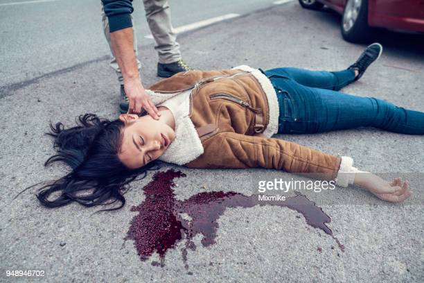 woman lying in blood on the road - mulher morta imagens e fotografias de stock