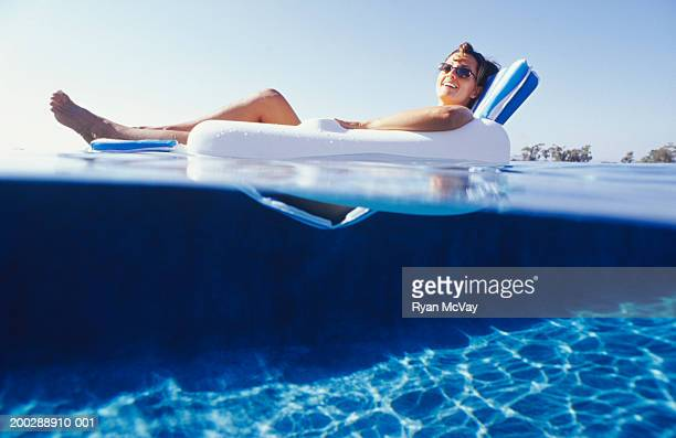 Woman lying in floating chair, surface view