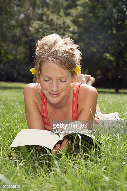 Woman lying in grass reading a book