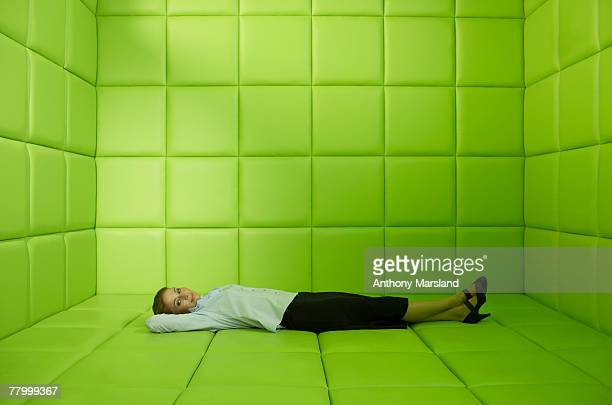 Woman lying in green padded cell