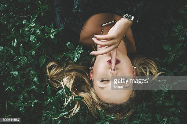 Woman lying in green plants outdoors