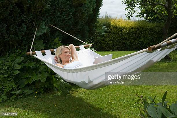 Woman lying in hammock with laptop