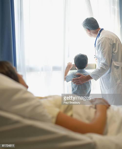 Frau liegen im Bett im Krankenhaus mit Arzt und Jungen