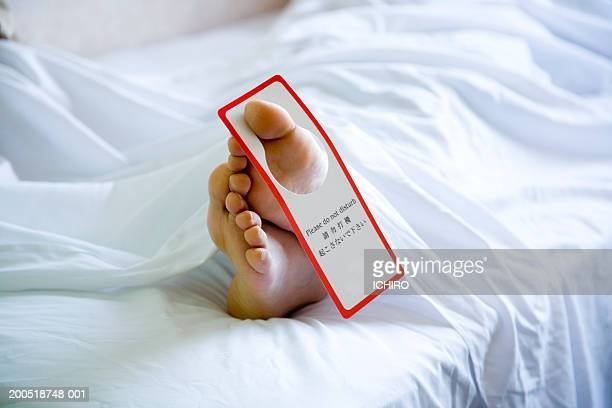 Woman lying in hotel bed, information sign hanging on toe, low section