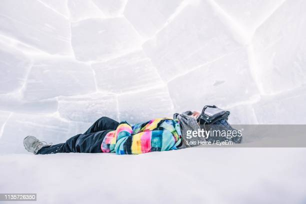 woman lying in igloo - igloo stock pictures, royalty-free photos & images
