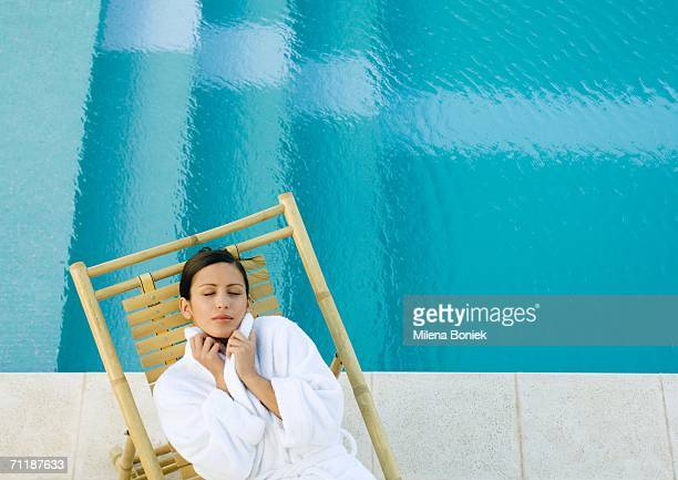 woman lying in lounge chair at edge of pool, wearing bathrobe - バスローブ ストックフォトと画像