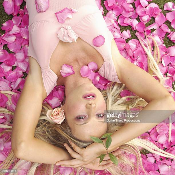 woman lying in pink rose petals - risque woman stock photos and pictures