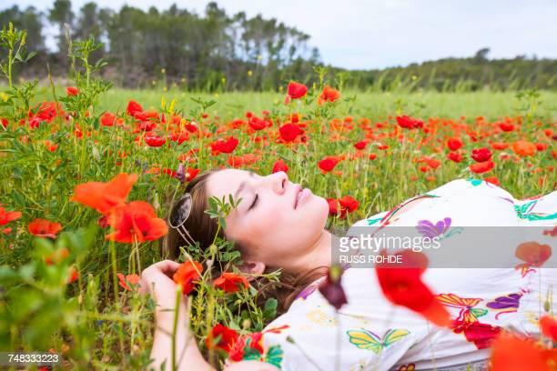 Woman lying in poppy field with eyes closed, Palma de Mallorca, Islas Baleares, Spain, Europe
