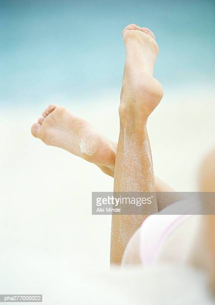 woman lying in sand, close-up of lower legs - woman lying on stomach with feet up stock photos and pictures