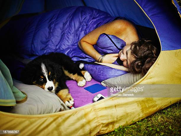 Woman lying in sleeping bag in tent with puppy