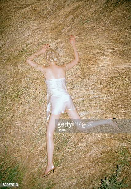 a woman lying in straw - women in slips stock photos and pictures