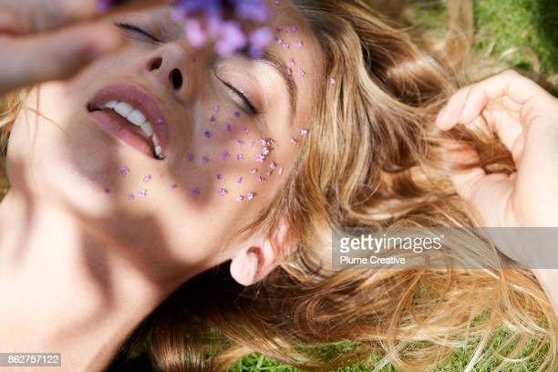 Woman lying in sun with flowers on her face