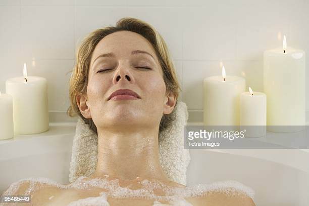 A woman lying in the bathtub surrounded by candles