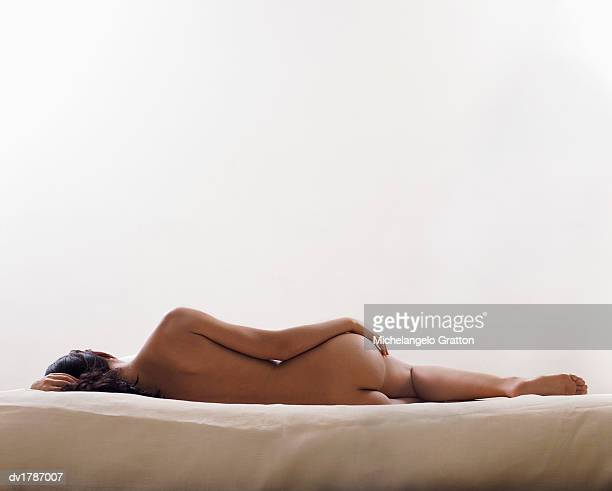 woman lying naked on one side on a bed - donna nuda sdraiata foto e immagini stock