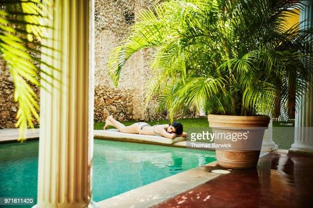 Woman lying next to pool in courtyard of outdoor spa