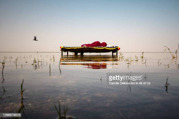 Woman lying on a bed above the water on Avril 22, 2016 in Thatta, Sindh, Pakistan.
