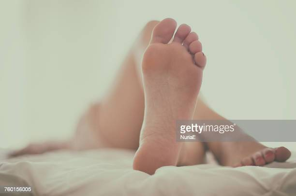 woman lying on a bed - female feet soles stock photos and pictures