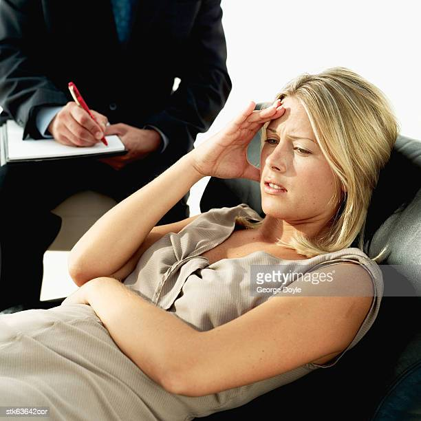 woman lying on a couch beside a man writing in a notebook - psychiatrist's couch stock pictures, royalty-free photos & images