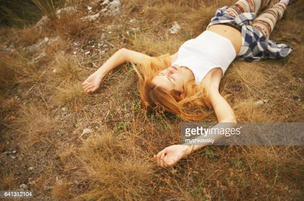 Woman lying on a grass in the mountains