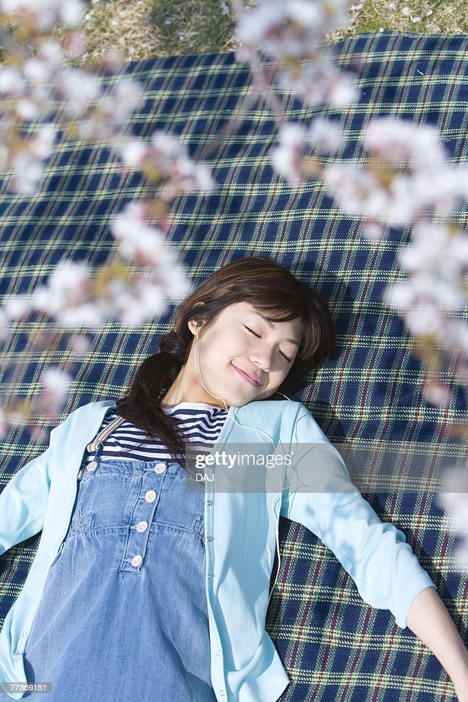 Woman lying on a leisure sheet under the cherry tree, closing eyes, high angle view, differential focus, Japan : Photo