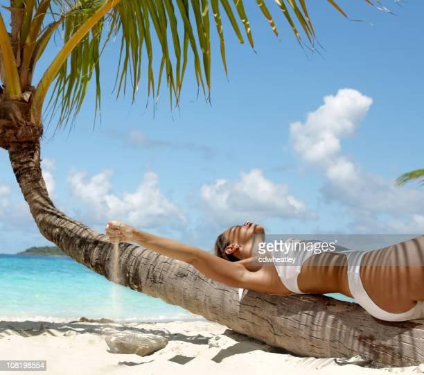 Frau auf einer Palme am Strand am Karibischen Meer