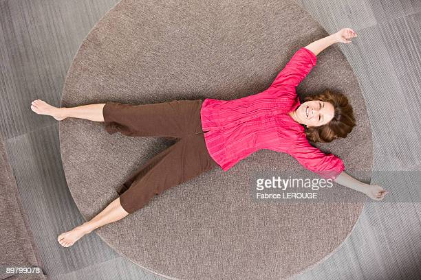 woman lying on a round sofa - lying on back photos stock pictures, royalty-free photos & images