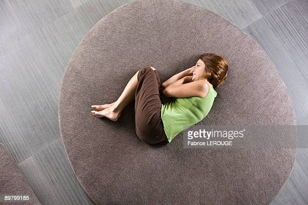 Woman lying on a round sofa