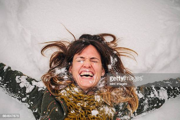 A woman lying on a snow bank with her arms stretched out.